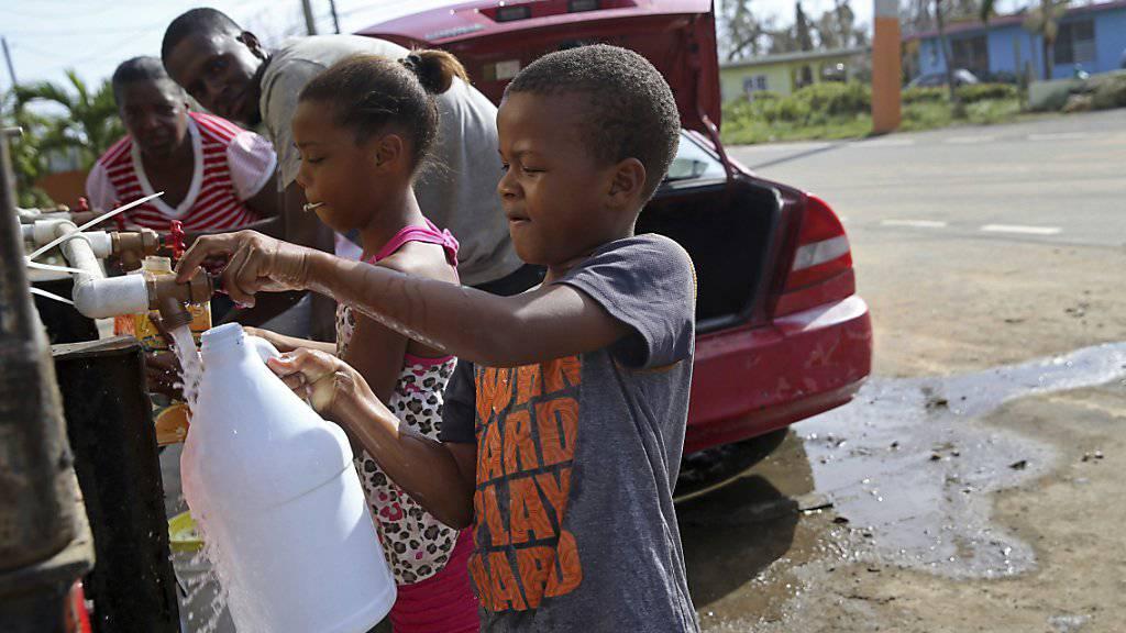 Kinder füllen Wasser in Flaschen auf Puerto Rico. Die Infrastruktur der Karibikinsel ist nach dem Durchzug von Hurrikan «Maria» schwer beschädigt.