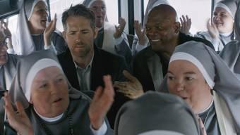 """Ryan Reynolds (l) und Samuel L. Jackson (r) haben's in """"Hitman's Bodyguard"""" lustig mit einem Geschwader Klosterfrauen. Der Film war am Wochenende der meistbesuchte in Nordamerika. (zVg)"""