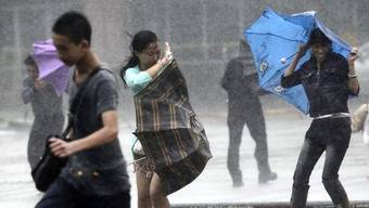 Die Menschen auf der Insel Hainan versuchen dem Sturm zu trotzen