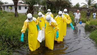 Die Gefahr lauert beim unvorsichtigen Ablegen kontaminierter Schutzkleider: Helfer in Liberia bringen den Leichnam eines an Ebola erkrankten Menschen weg. Ahmed jallanzo/epa/keystone