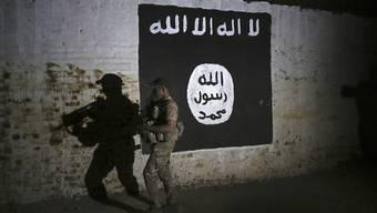 Ein irakischer Soldat inspiziert einen Eisenbahntunnel mit einer aufgemalten Flagge der Terrormiliz Islamischer Staat (IS). (Archivbild)