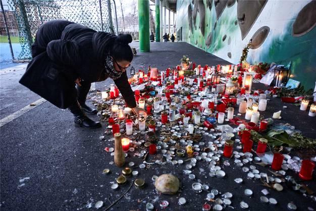 """Eine Frau zündet eine Kerze für Georg an, der am 20. Dezember 2017 unter der Dreirosenbrücke in Basel mit einer Stichwaffe getötet wurde. Sturm """"Burglind"""" blies einige Lichter aus."""