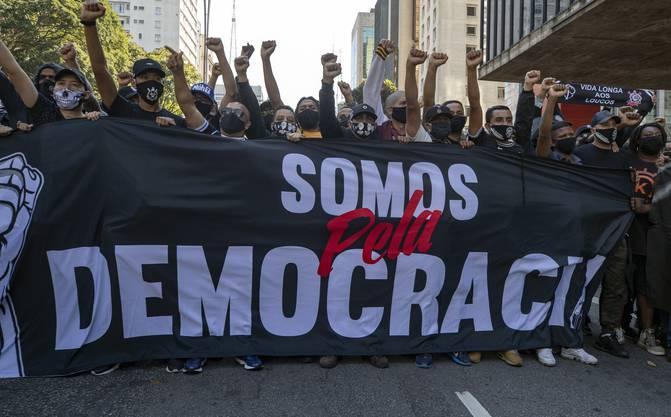 Fans von zwei verschiedenen Fussballklubs halten bei einem Protest gegen die Regierung ein Banner mit der Aufschrift «Wir sind für Demokratie».