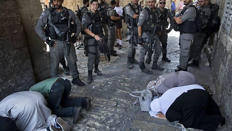 Muslimische Gläubige beten in der Jerusalemer Altstadt, beobachtet von israelischen Grenzpolizisten.