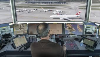 Ein Mitarbeiter von Skyguide kontrolliert die Monitore und hat Blick auf das Flugfeld, bei Skyguide im Tower des Flughafen Zuerich Kloten.