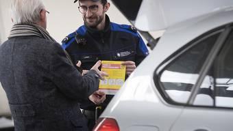 Ein Mitarbeiter der Bundeszollverwaltung verteilt an der schweizerisch-italienischen Grenze Broschüren über die Präventionskampagne des Bundesamtes für Gesundheit (BAG) gegen die Ausbreitung des Coronavirus COVID-19.