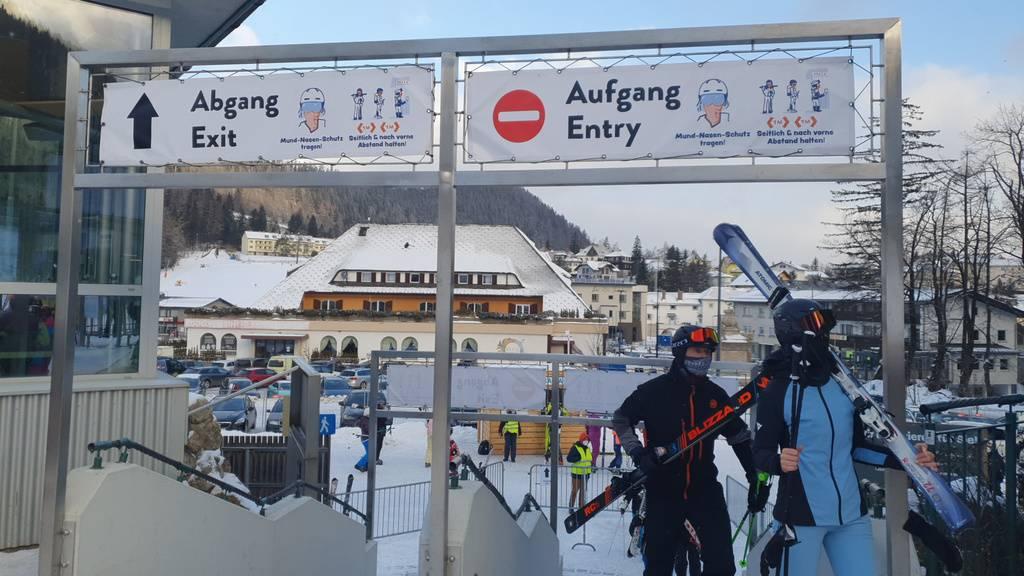 Skifahrer gehen in Semmering unter Schildern, die auf die coronabedingten Hygieneregeln hinweisen, durch.