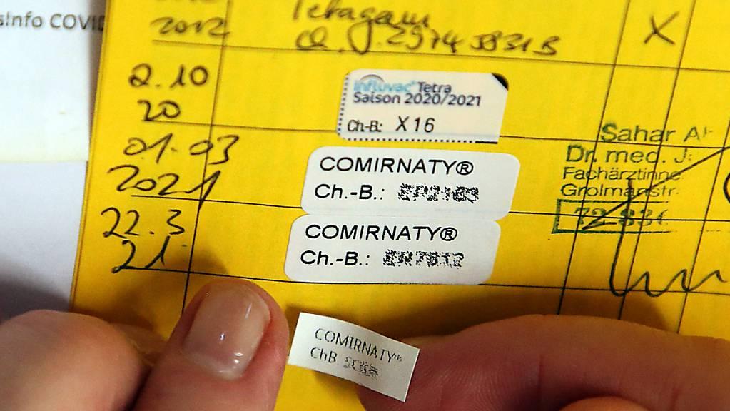 Eine Ärztin klebt den Nachweis für die dritte Impfung mit dem Comirnaty-Impfstoff des Herstellers Biontech/Pfizer in ein Impfbuch. Menschen mit geschwächtem Immunsystem sollen laut einem internationalen Expertengremium der WHO eine dritte Dosis des Corona-Impfstoffs erhalten.