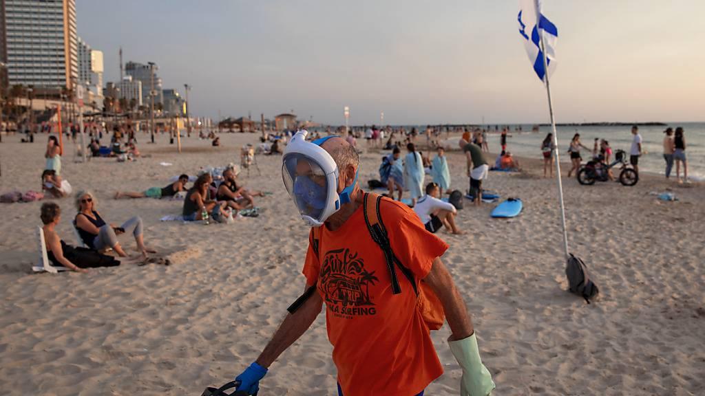 Ein älterer Mann trägt Handschuhe und eine Tauchermaske, die er als schützende Gesichtsmaske an der Strandpromenade verwendet. Foto: Oded Balilty/AP/dpa