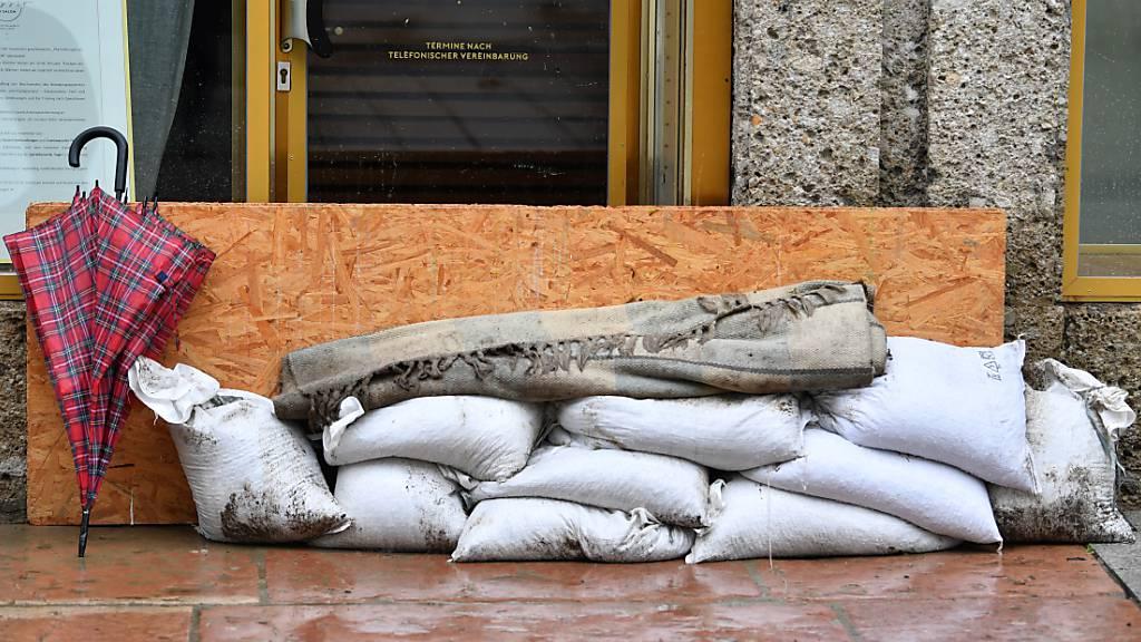 Sandsäcke liegen vor dem Eingang eines Ladens in Hallein. Foto: Barbara Gindl/APA/dpa