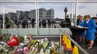 Eine Stewardess trägt sich am Amsterdamer Flughafen Schiphol ins Kondolenzbuch ein. Währendem versammeln sich Angehörige und wollen zur Absturzstelle fliegen.