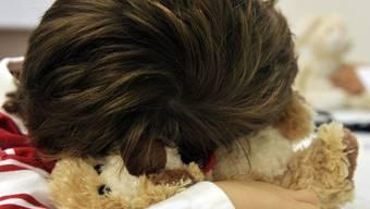 Ein Kind ruht sich auf einem Kuscheltier aus (Symbolbild)