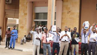 Generalstreik gegen Generäle: Demonstranten verlangen vor der Bank of Khartoum in der sudanesischen Hauptstadt den raschen Übergang zu einer Zivilregierung.