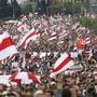 Demonstranten nehmen an einer Kundgebung der Opposition teil und schwenken die historische Nationalflagge des Landes. Trotz eindringlicher Warnungen vor neuen Protesten gegen Staatschef Lukaschenko sind wieder Tausende Menschen in der Hauptstadt Minsk unterwegs. Foto: -/Tut.by/AP/dpa