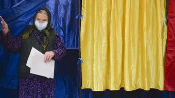 Eine Frau mit Mund-Nasen-Schutz verlässt eine Wahlkabine, nachdem sie bei den Parlamentswahlen ihre Wahlstimme abgegeben hat. Foto: Alexandru Dobre/AP/dpa
