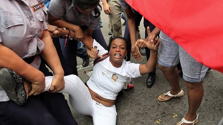 Sicherheitskräfte nehmen eine Kubanerin fest, die der Oppositionsgruppe Ladies in White angehört - am Tag der Menschenrechte.