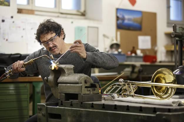 Tschirren arbeitet am Aufsatz, mit dem die Posaune an der Schulterplatte befestigt werden kann.