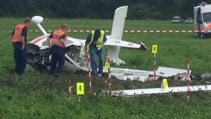 Einsatzkräfte der Polizei untersuchen das abgestürzte Flugzeug.