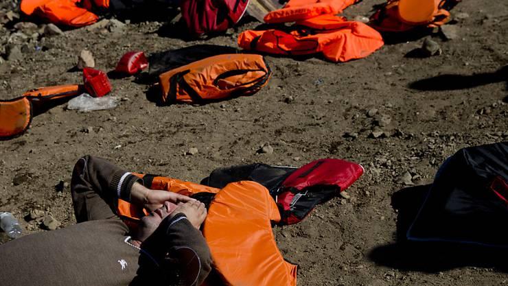 Auch für ihn gingen in St. Gallen Hunderte auf die Strasse: Ein syrischer Flüchtling liegt erschöpft am Strand der griechischen Insel Lesbos, nachdem er die Überfahrt von der türkischen Küste überstanden hat (Symbolbild).