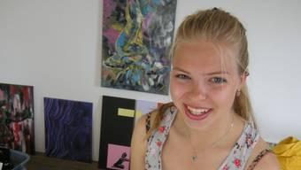 Saima Sägesser mit ihrem Skizzenbuch und im Hintergrund an der Wand einer aktuellen Arbeit.  uby