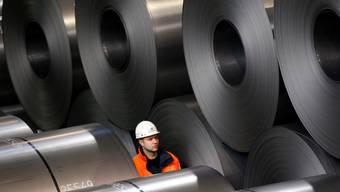 Ein Mitarbeiter von Thyssenkrupp inmitten von Rohstahlrollen im Stahlwerk von Duisburg. (Archiv)