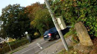 Alte und neue Grenzwächter: Eine Kamera über einem Grenzstein im St. Johann. Die Grenze verläuft quer über die Strasse und folgt dem Weg im Hintergrund.