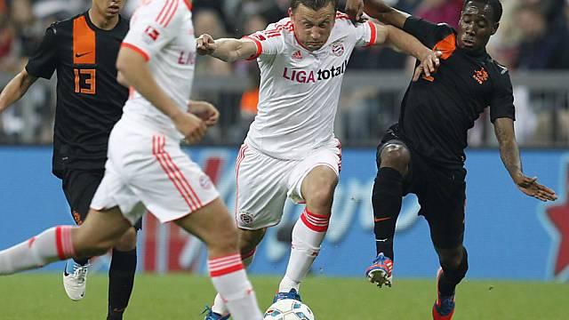 Bayerns Ivica Olic schüttelt seinen Gegenspieler Vurnon Anita ab.