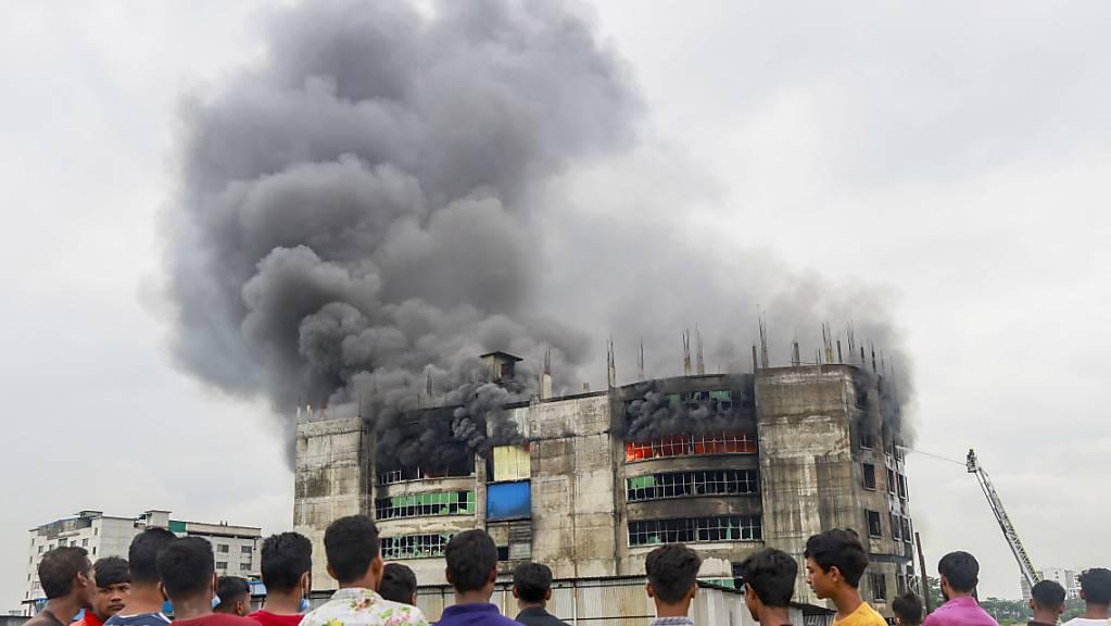 Menschen sehen zu, wie während des Brands in einer Fabrik Rauch von dem Gebäude aufsteigt. Bei einem Brand in einer Lebensmittel- und Getränkefabrik außerhalb der bangladeschischen Hauptstadt Dhaka sind mindestens 52 Menschen getötet worden. Foto: Suvra Kanti Das/ZUMA Wire/dpa