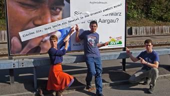 Drei junge Grüne kritisieren SVP-Slogans: Irène Kälin (Grossrätin), Ömer Oral (Präsident) und Sebastian Knecht (Vorstandsmitglied) vor dem überklebten Wahlplakat am Wohler Bahnhof.