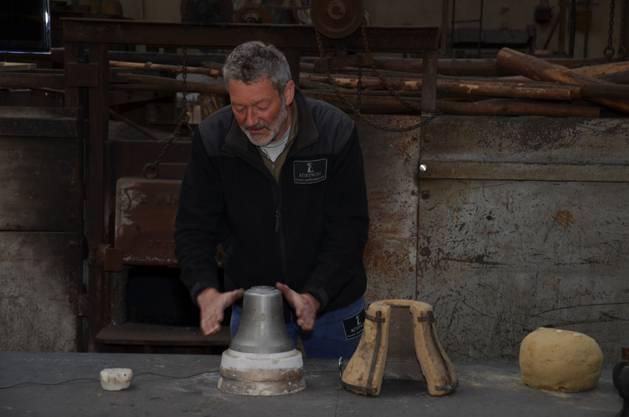 Bolliger erklärt, wie der äussere Teil der Gusform vor dem Guss befestigt werden muss.
