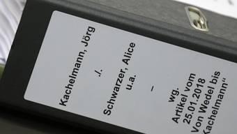 """Ein Aktenordner """"Kachelmann, Jörg - Schwarzer, Alice"""" liegt im Düsseldorfer Landgericht auf einem Tisch. Bei der Verhandlung wird ein Streit zwischen Wetterexperte Jörg Kachelmann und der Publizistin Alice Schwarzer verhandelt."""