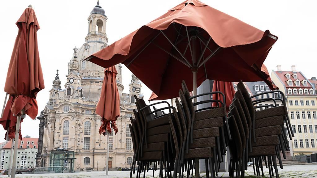 Leere Stühle stapeln sich vor einem Restaurant auf dem Neumarkt vor der Dresdener Frauenkirche. Die Menschen in Deutschland müssen sich ab dem Wochenende auf neue Corona-Beschränkungen einstellen. Foto: Sebastian Kahnert/dpa-Zentralbild/dpa