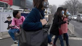 Gegen Smog: Fussgängerinnen mit Atemschutzmasken in Peking (Archiv)