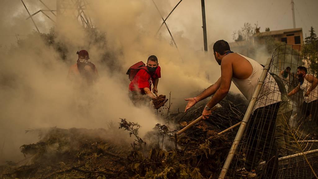 Freiwillige Helfer versuchen einen Waldbrand in einem Waldgebiet nördlich von Athen zu löschen. Foto: Angelos Tzortzinis/dpa