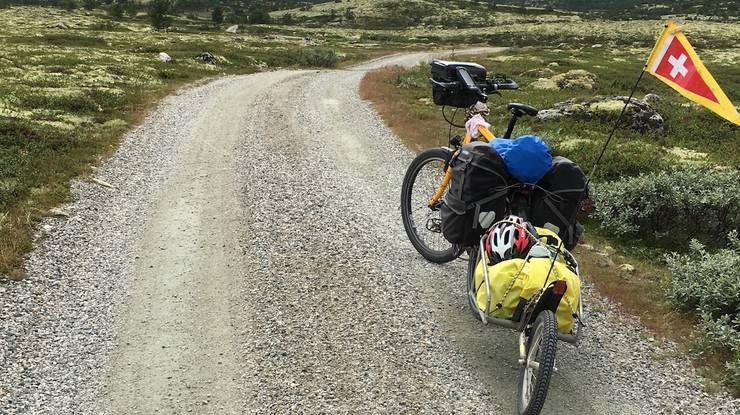 Alles dabei, was es für einen Roadtrip braucht: Velo mit Anhänger und Schweizer Fähnchen.