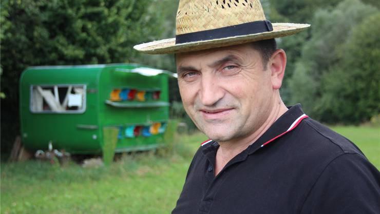 Bajram Mulaj vor dem zum Bienenhaus umgebauten Wohnwagen. wpo