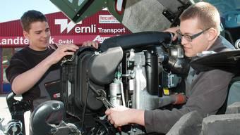 Pascal Wietlisbach (2. Lehrjahr, links) und Dominik Strebel (4. Lehrjahr) an der Arbeit am Traktor.mhu