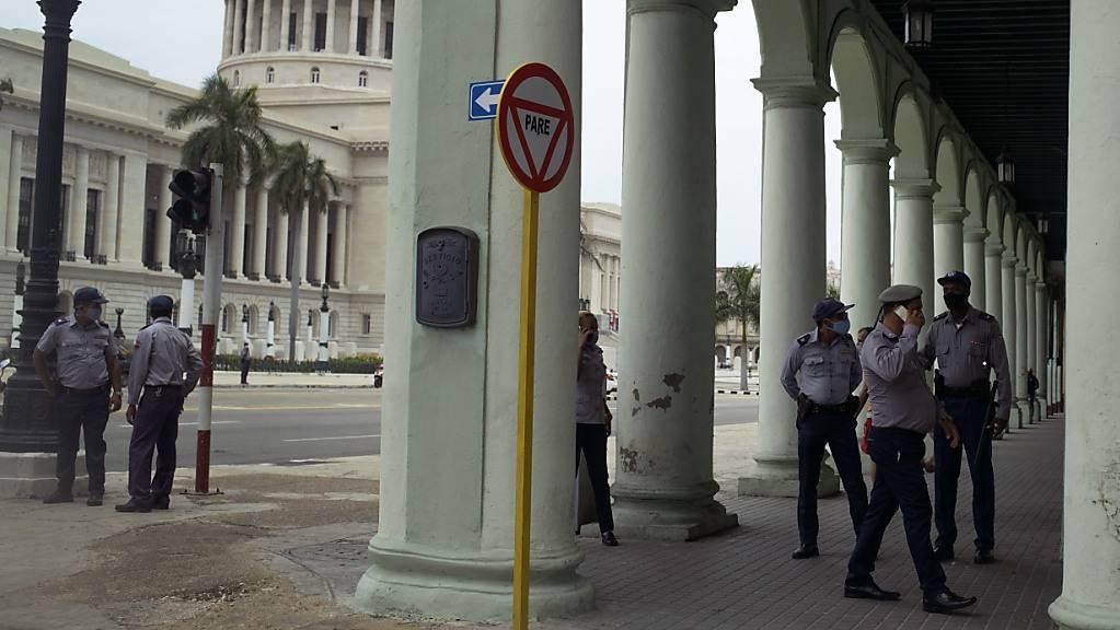 Polizisten stehen Wache in der Nähe des Kapitols. Drei Tage nach Beginn der Demonstrationen gegen die Regierung in Kuba sind nach Angaben unabhängiger Journalisten inzwischen Tausende Menschen festgenommen worden. Foto: Eliana Aponte/AP/dpa