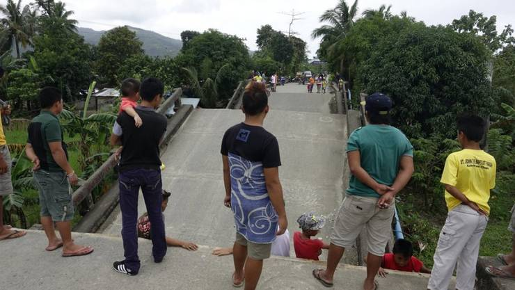 Anwohner betrachten eine durch das Erdbeben beschädigte Brücke in der Stadt Surigao auf der philippinischen Insel Mindanao.