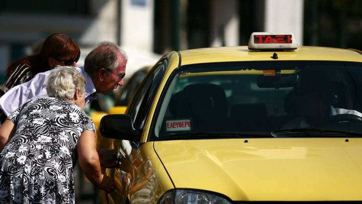 Ein älteres Paar sucht in Athen nach einem leeren Taxi. In der griechischen Hauptstadt und in Thessaloniki sind die Taxifahrer am Mittwoch in einen 24-stündigen Streik getreten. (Archiv)