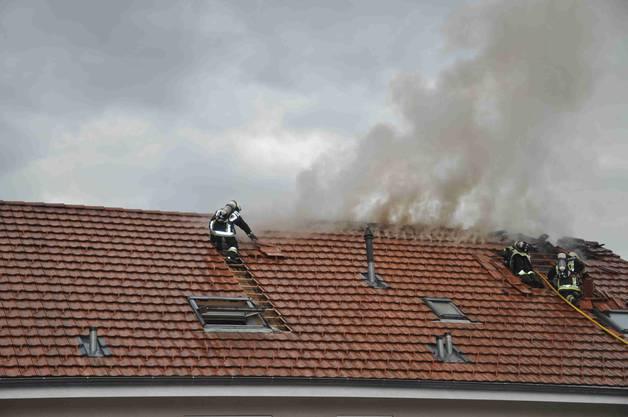 Die Feuerwehr deckt das Dach teilweise ab, um an den Brandherd zu gelangen.