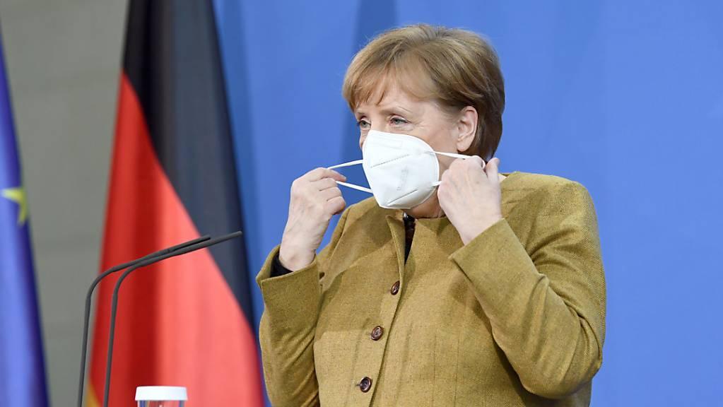 ARCHIV - Bundeskanzlerin Angela Merkel (CDU) zieht sich vor einer Pressekonferenz im Anschluss an den virtuellen G7-Gipfel im Februar 2021 eine Maske an. Foto: Annegret Hilse/Reuters/Pool/dpa Foto: Annegret Hilse/Reuters/Pool/dpa