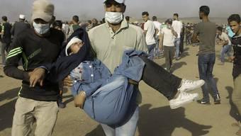Palästinensische Sanitäter und Demonstranten evakuieren eine verletzte Jugendliche.
