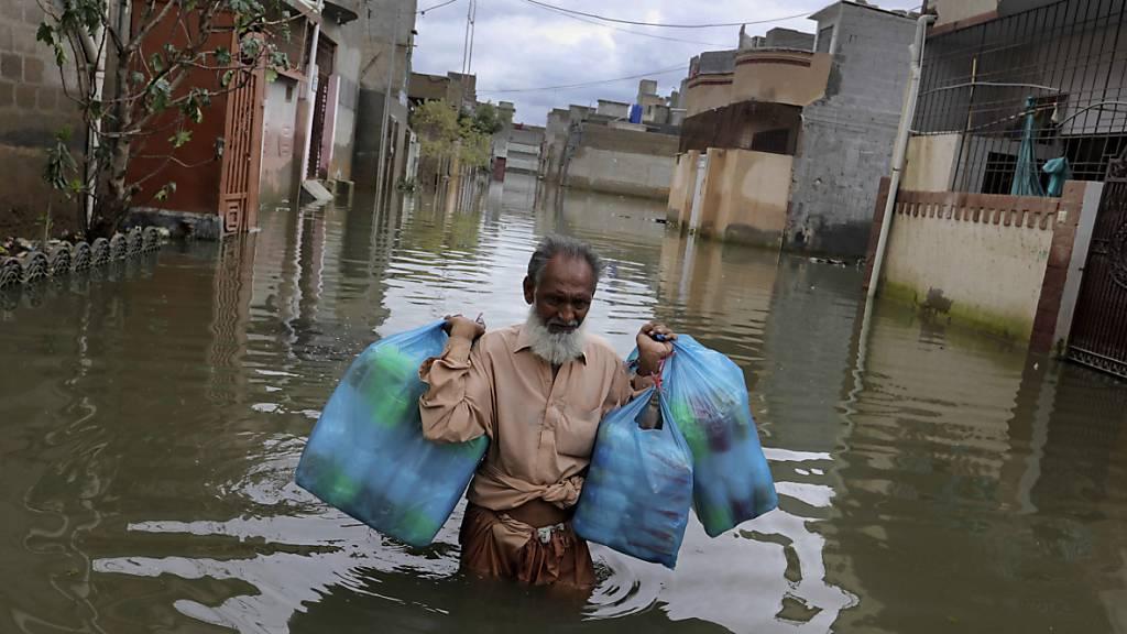 Ein Mann trägt Waren, während er nach heftigen Regenfällen durch eine überflutete Straße watet. Nach Überschwemmungen in Pakistans Millionenstadt Karatschi sind in den vergangenen drei Tagen mindestens 41 Menschen ums Leben gekommen. Foto: Fareed Khan/AP/dpa
