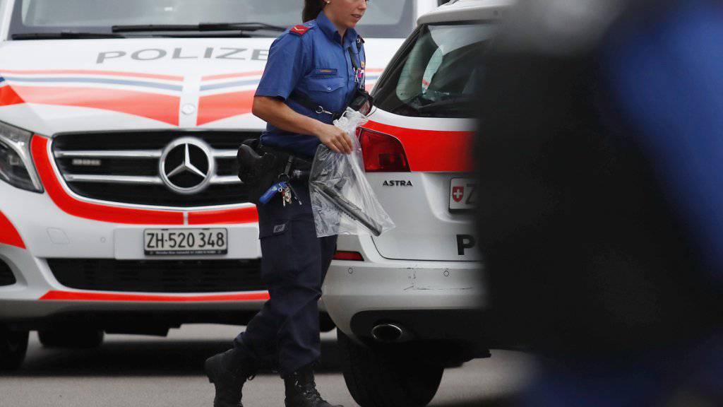 Nach dem Einsatz in Dübendorf wegen eines bewaffneten Mannes: Eine Kantonspolizistin bringt eine Waffe weg.