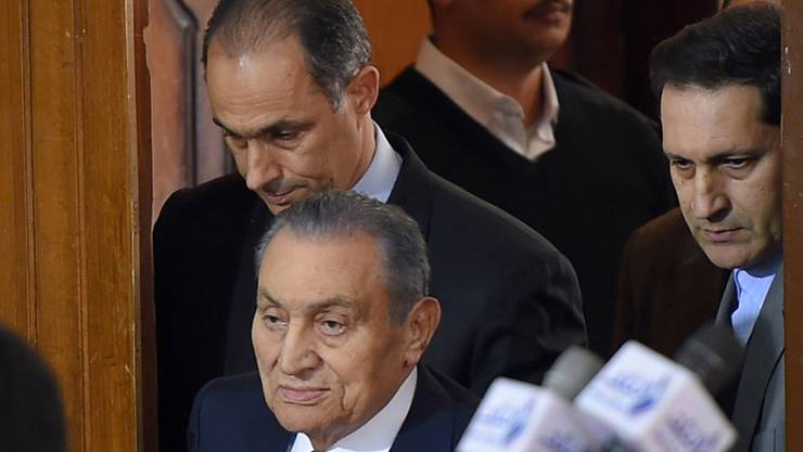 Husni Mubarak (unten), flankiert von seinen Söhnen Gamal (links - oder hinter ihm) Alaa (ganz rechts) im Gerichtssaahl in Kairo.