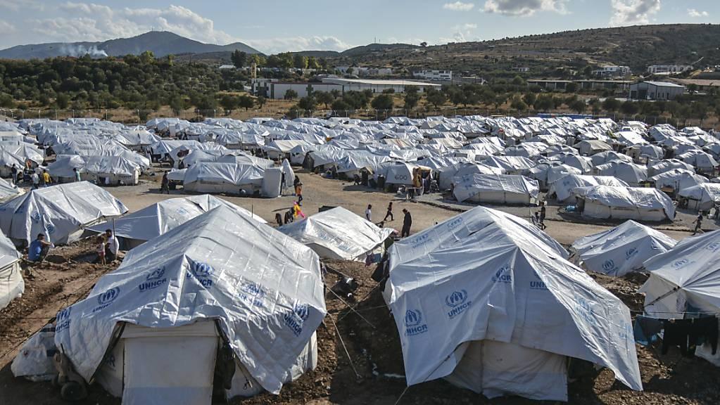 Migranten gehen nach starken Regenfällen durch das Flüchtlingslager «Kara Tepe». F
