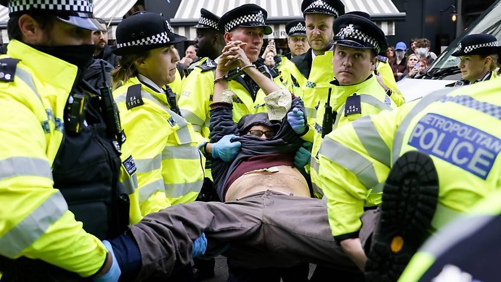 Polizisten verhaften einen Demonstranten, der sich während eines von der Umweltschutzbewegung Extinction Rebellion organisierten Protests unter einen Lieferwagen klebte. Bei der Protestaktion in London laut Mitteilung von Scotland Yard am späten Montagabend mehr als 50 Menschen festgenommen worden.