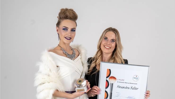 Alexandra Keller zeigt zusammen mit ihrem Model Urkunde und Pokal.