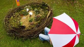 Person mit Regenschirm vor einem riesigen Osternest (Archivbild)